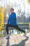Young Male Runner Stretching in the Park in Cold Sunny Autumn Morning. Healthy Lifestyle and Sport Concept. Young Male Runner Stretching in the Park in Cold Stock Image