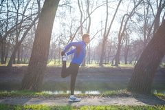 Young Male Runner Stretching in the Park in Cold Sunny Autumn Morning. Healthy Lifestyle and Sport Concept. Young Male Runner Stretching in the Park in Cold Royalty Free Stock Image