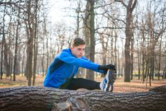 Young Male Runner Stretching in the Park in Cold Sunny Autumn Morning. Healthy Lifestyle and Sport Concept. Young Male Runner Stretching in the Park in Cold Royalty Free Stock Photography