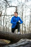 Young Male Runner Stretching in the Park in Cold Sunny Autumn Morning. Healthy Lifestyle and Sport Concept. Young Male Runner Stretching in the Park in Cold Royalty Free Stock Photo