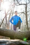 Young Male Runner Stretching in the Park in Cold Sunny Autumn Morning. Healthy Lifestyle and Sport Concept. Young Male Runner Stretching in the Park in Cold Stock Photos