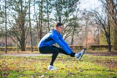 Young Male Runner Stretching in the Park in Cold Sunny Autumn Morning. Healthy Lifestyle and Sport Concept. Young Male Runner Stretching in the Park in Cold Stock Photography