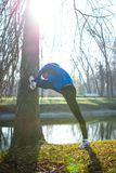 Young Male Runner Stretching in the Park in Cold Sunny Autumn Morning. Healthy Lifestyle and Sport Concept. Young Male Runner Stretching in the Park in Cold Stock Images