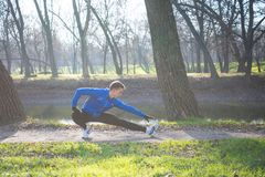Young Male Runner Stretching in the Park in Cold Sunny Autumn Morning. Healthy Lifestyle and Sport Concept. Young Male Runner Stretching in the Park in Cold Royalty Free Stock Photos