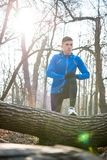 Young Male Runner Stretching in the Park in Cold Sunny Autumn Morning. Healthy Lifestyle and Sport Concept. Young Male Runner Stretching in the Park in Cold Stock Photo