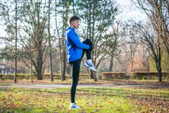 Young Male Runner Stretching in the Park in Cold Sunny Autumn Morning. Healthy Lifestyle and Sport Concept. Young Male Runner Stretching in the Park in Cold Royalty Free Stock Images