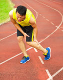 Young male runner suffering from leg cramp on the track. In the stadium Stock Photos