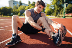 Young male runner suffering from leg cramp on the track. At the stadium Royalty Free Stock Image