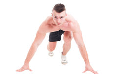 Young male runner taking ready to start position. Facing the camera and isolated on white. Sprinting or running with determination concept Stock Images