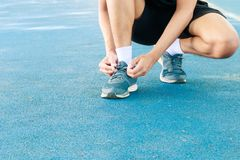 Free Young Male Runner Tying Shoelaces Old In Runner Exercise For Health Lose Weight Concept On Track Rubber Cover Blue Public Park Stock Photography - 120972972