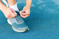Young male runner tying shoelaces old in runner exercise for health lose weight concept on track rubber cover blue public park.  Stock Photography