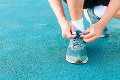 Young male runner tying shoelaces old in runner exercise for health lose weight concept on track rubber cover blue public park.  Stock Photos