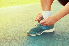 Young male runner tying shoelaces old in runner exercise for health lose weight concept on track rubber cover blue public park.  Stock Photo