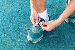 Young male runner tying shoelaces old in runner exercise for health lose weight concept on track rubber cover blue public park.  Stock Image