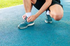Young male runner tying shoelaces old in runner exercise for health lose weight concept on track rubber cover blue public park.  Stock Images