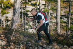 Young male runner with walking poles climbs a mountain path up. Yalta, Russia - November 4, 2015: young male runner with walking poles climbs a mountain path up Stock Photography