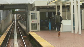 Young male running railway station. Student hurrying up on train platform stock video footage