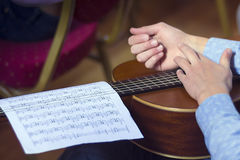 Young male's hands and guitar with musical scores Royalty Free Stock Images