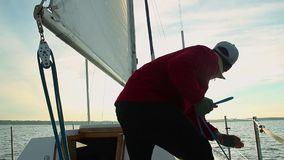 Young male sailor helping out senior captain on sailing boat. Stock footage stock video footage