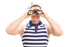 Young male sailor looking through binoculars. Portrait of a young male sailor looking through binoculars isolated on white background Stock Photography