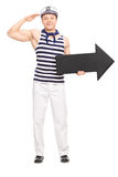 Young male sailor saluting and holding an arrow. Full length portrait of a young male sailor saluting towards the camera and holding a big black arrow pointing Stock Photography