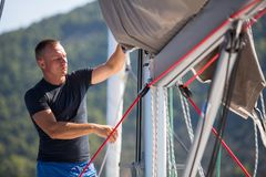 A young male sailor setting sail on his yacht. Sport. A young male sailor setting sail on his yacht Stock Image