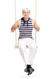 Young male sailor sitting a swing. Vertical shot of a young male sailor sitting a swing and looking at the camera isolated on white background Stock Image
