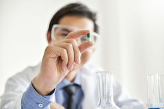 Young male scientist holding a pill. Asian Male Research is working in the Laboratory. Happiness Royalty Free Stock Images