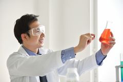 Young male scientist holding a pill. Asian Male Research is working in the Laboratory. Happiness Stock Images