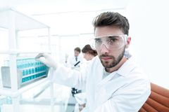 Young male scientist looking at a sample in a test tube side vie Royalty Free Stock Photography