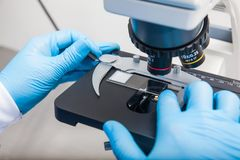 Male scientist looking at slides under the microscope. Young male scientist looking at slides under the microscope Royalty Free Stock Photo