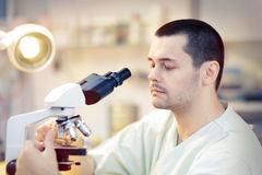 Young Male Scientist with Microscope. Portrait of a male doctor looking through a microscope in a laboratory Stock Photo