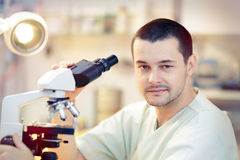 Young Male Scientist with Microscope. Portrait of a male doctor looking through a microscope in a laboratory Stock Photography