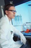 Young male scientist sitting by the cell culture hood Stock Photo