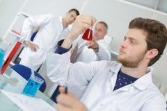 Young male scientist takes aliquote liquid sample. Young male scientist takes an aliquote of liquid sample Stock Photo