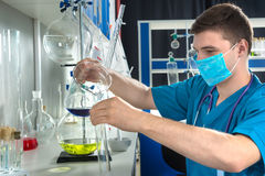 Young male scientist in uniform wearing a mask is holding test g. Lass and filling a test tube with blue liquid, making some research in a laboratory. Healthcare Royalty Free Stock Images