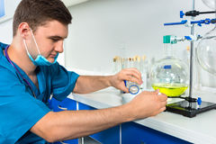 Young male scientist in uniform wearing a mask is working with c. Hemistry flasks and making some research in a laboratory. Healthcare and biotechnology concept Stock Photography