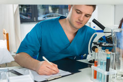 Young male scientist in uniform is writing down notes of his res. Earch after looking through a microscope in a laboratory. Healthcare and biotechnology concept Stock Photography