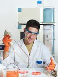 Young male scientist works with cultured cells in research labor. Young energetic male scientist working with cultured cells smiles at the camera. Shallow DOF Stock Photography
