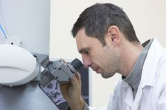 Young male scientist works with a microscope in a science lab stock photography