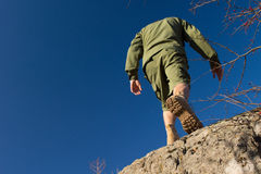 Young Male Scout Climbing on Old Rock Royalty Free Stock Photography