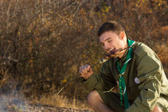 Young Male Scout Eating Grilled Sausage Royalty Free Stock Photos
