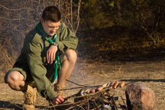Young Male Scout Grilling Sausages at the Camp Stock Photography