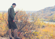 Young Male Scout Navigating a Compass Device. Serious Young Male Scout Navigating a Compass Device for a Direction at the Wilderness Stock Photos