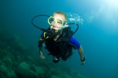 Young male scuba diver swims over reef Stock Photos
