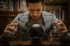 Young male seer predicting the future by looking into crystal ball. Handsome young man predicting the future by looking into black crystal ball Stock Photos