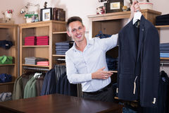 Young male seller displaying diverse cloths. In  store Stock Photos