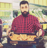 Young male seller offering carrots. In grocery shop Stock Photography