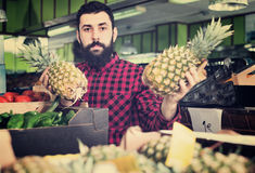 Young male seller offering pineapples. In grocery shop Royalty Free Stock Photo