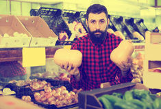 Young male seller offering potatoes. Glad cheerful positive male seller offering potatoes in grocery shop Royalty Free Stock Images